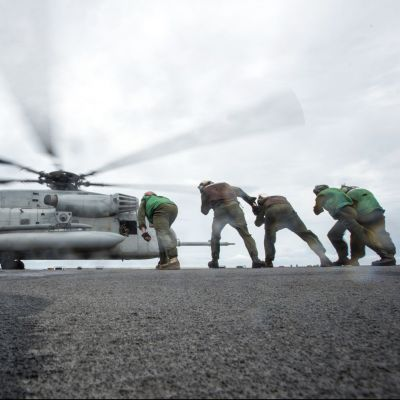 161006-N-WF272-093 SOUTH CHINA SEA (Oct. 6, 2016) Marines, assigned to Marine Medium Tiltrotor Squadron (VMM) 262, lean into the rotor wash of a CH-53E Super Stallion as it takes off from the flight deck of amphibious assault ship USS Bonhomme Richard (LHD 6). Bonhomme Richard, flagship of the Bonhomme Richard Expeditionary Strike Group, is operating in the South China Sea in support of security and stability in the Indo-Asia Pacific region. (U.S. Navy photo by Petty Officer 2nd Class Diana Quinlan/Released)